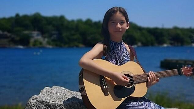 Xuan Trzebiatowski avec sa guitare, sur le bord de l'eau