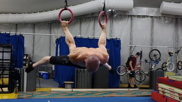 L'image montre un athlète de cirque suspendu à des anneaux.