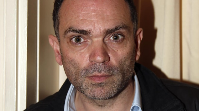 Yann Moix posant devant un rideau jaune.