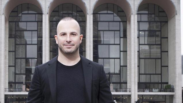 Un homme, en veston et t-shirt noirs, se tient debout devant les fenêtres en forme d'arches d'un édifice.