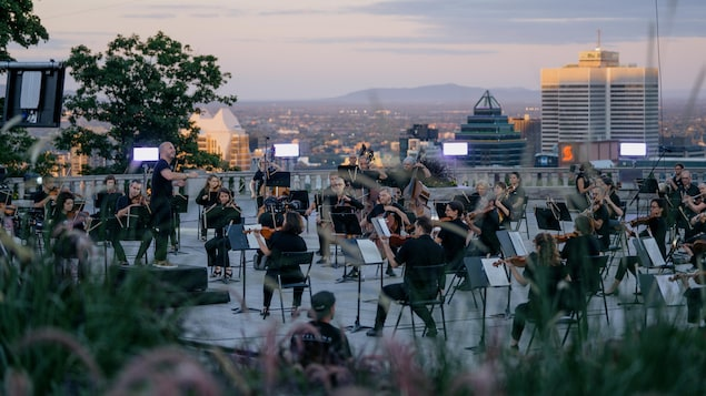 Les musiciennes et les musiciens sont devant le chalet et on voit Montréal derrière eux.