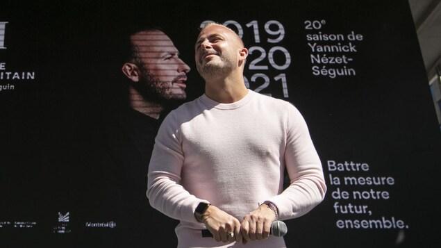 Le maestro Yannick Nézet-Séguin devant une affiche de l'Orchestre métropolitain de Montréal.