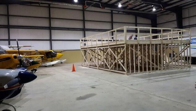 Des travailleurs construisent une plate-forme en bois dans le hangar