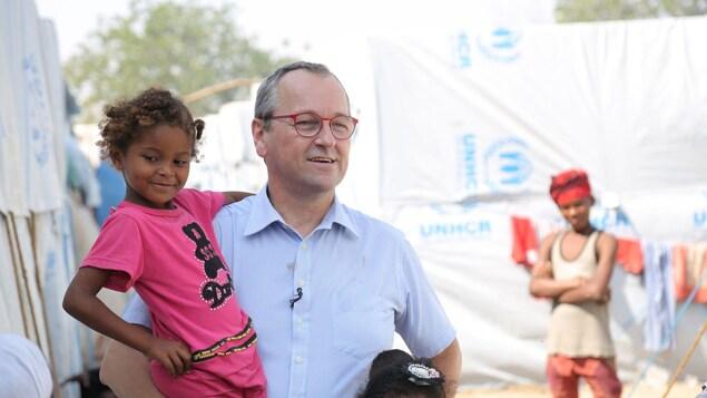 Un homme tient une fillette souriante dans ses bras.