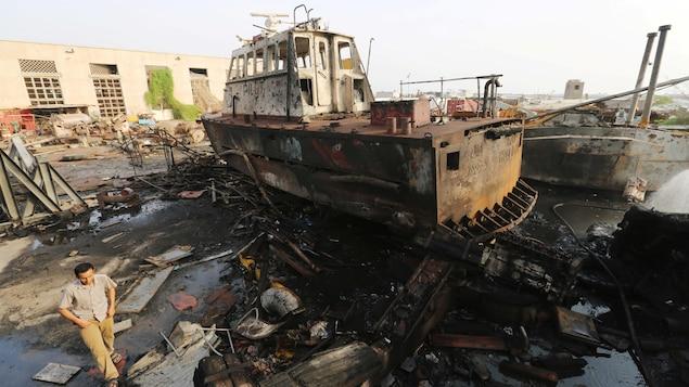 Un homme marche près d'un bateau calciné et de débris.