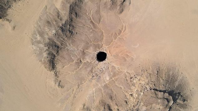 Vue aérienne éloignée du puits de Barhout : un trou noir au milieu du désert.