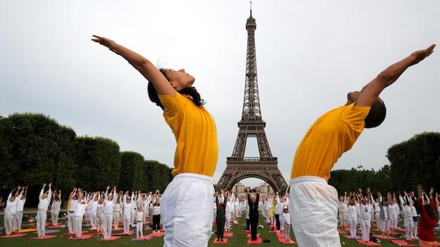 Des centaines d'adeptes du yoga dans les jardins au pied de la tour Eiffel.