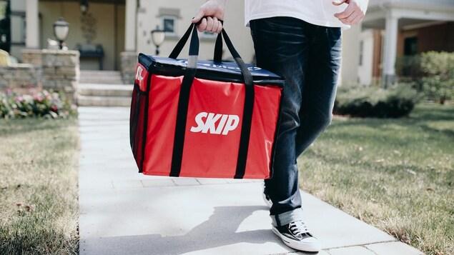 Un homme marche avec un sac de livraison rouge.