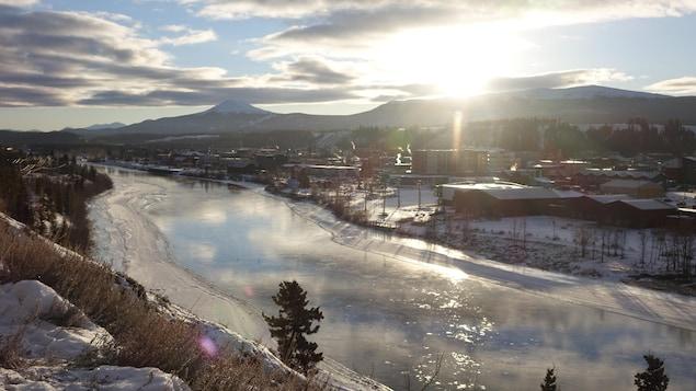 Le soleil au-dessus de Whitehorse avec en avant-plan le fleuve Yukon.