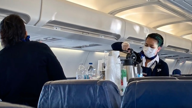 Des agentes de bord portent un masque