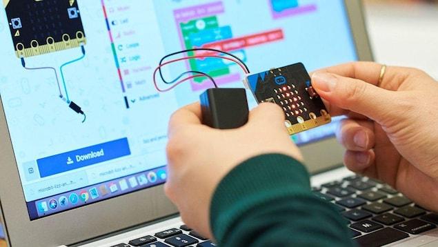 Zoom sur deux mains qui tiennent une pièce informatique raccrochée à un boitier par deux fils électriques. Derrière se trouve un écran d'ordinateur.