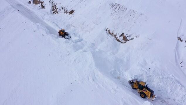 Vue des airs d'une section de la route où de la machinerie dégage de la neige.