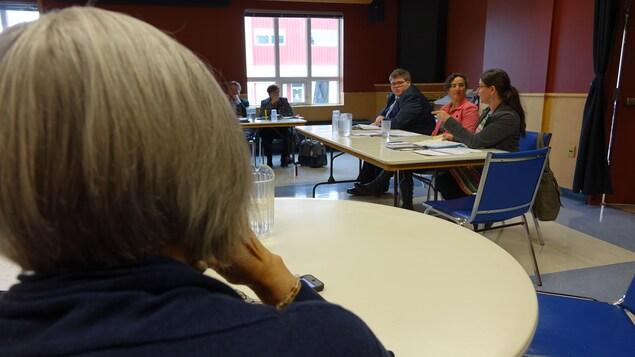 Sandra St-Laurent assisse à une table parle aux députés, une dame en avant-plan écoute