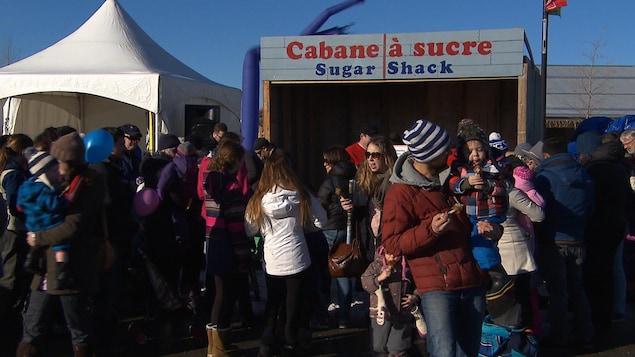 Une foule devant un kiosque qui affiche « cabane à sucre ».