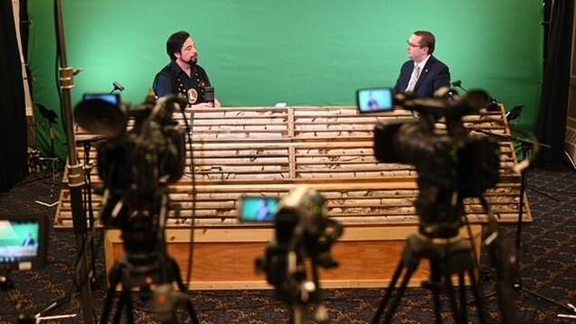 Deux hommes devant un écran vert et des caméras discutent.
