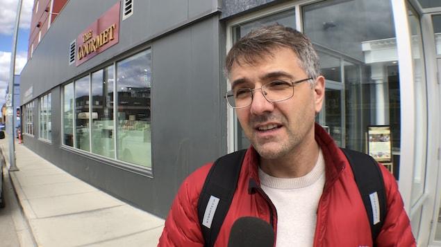 Gaël Marchand sur le trottoir devant un magasin.