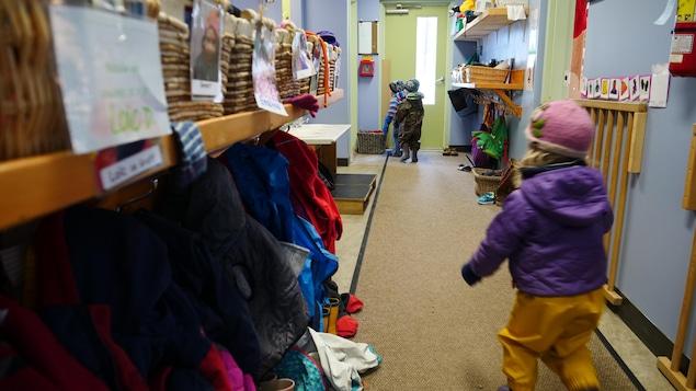 Un enfant court dans un couloir vers d'autres enfants.
