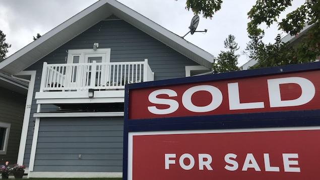 Affiche devant une petite maison vendue.
