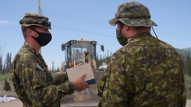 Deux soldats parlent sur le site des opérations.