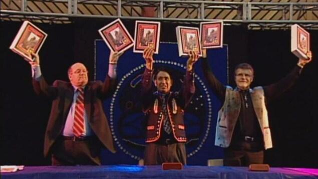 Trois hommes tiennent au bout de leur bras des copies d'un document sur une scène éclairée.