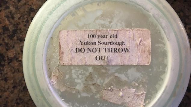 Le couvercle du récipient contenant le levain avec une étiquette indiquant qu'il s'agit d'un levain de 100 ans qu'il ne faut pas jeter.