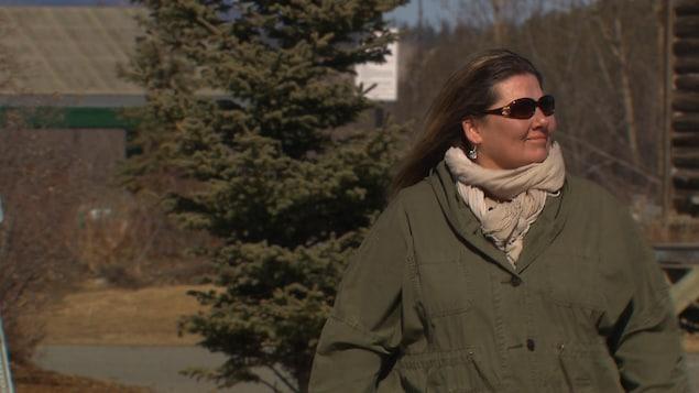 Une femme avec des lunettes fumées marche en regardant au loin.