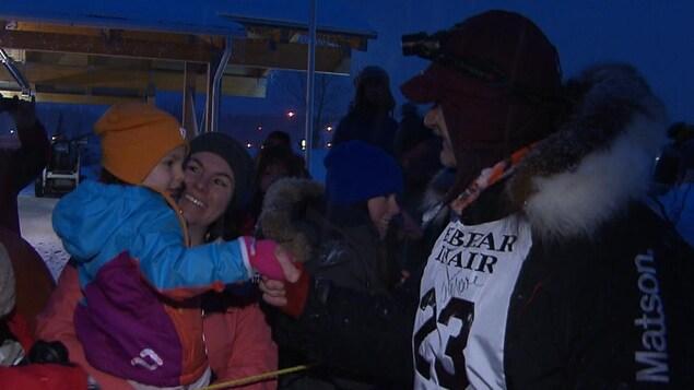 Allen Moore serre la main d'un enfant dans les bras de sa mère