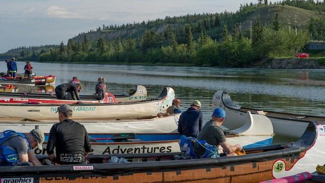 Des personnes sur des canoes au bord d'une rivière.