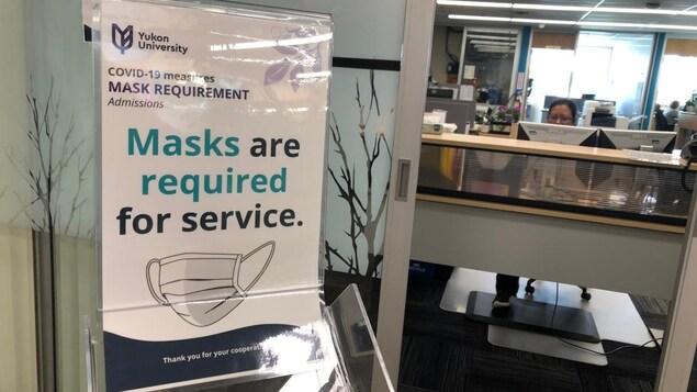 Affiche à l'entrée d'un bureau indiquant que le port du masque est obligatoire.