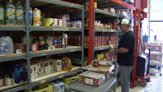 Une personne remplit des étagères de nourriture.