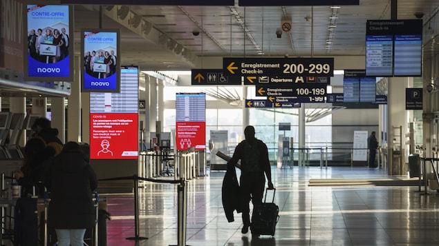 Un homme marche dans l'aéroport de Montréal.