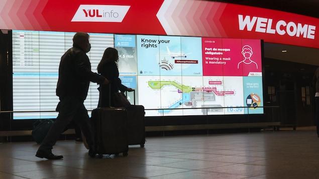 Un couple marche dans un corridor de l'aéroport Montréal-Trudeau.