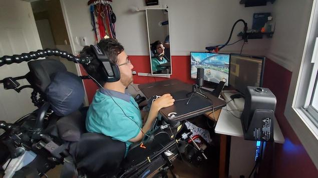 Un homme en fauteuil roulant joue au jeu vidéo «Rocket League» sur un ordinateur.