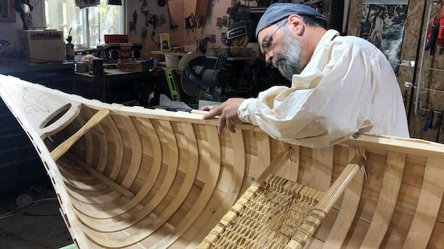 Yvan Tanguay sable un canot dans un atelier.