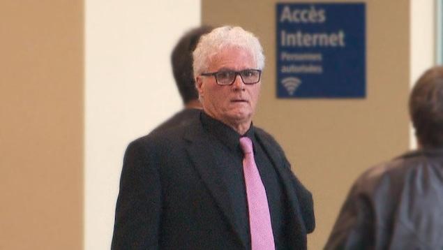Yves Colosse Plamondon, un homme aux cheveux blancs, regarde la caméra. Il porte une cravate rose et un complet noir.