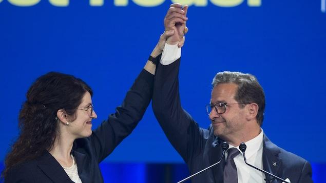 Yves-François Blanchet tient haut dans les airs la main de sa conjointe.