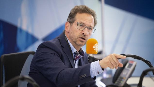 Le chef bloquiste, dans un studio de radio, pointe devant lui.