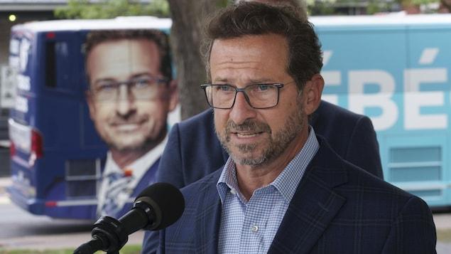 Yves-François Blanchet s'adresse aux médias devant son autobus de campagne.