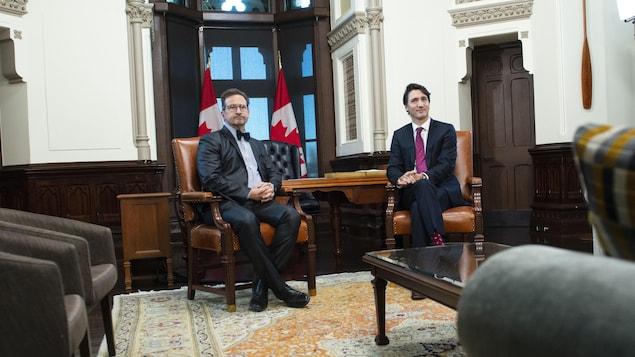 MM. Blanchet et Trudeau assis côte à côte dans une salle remplie de fauteuils.