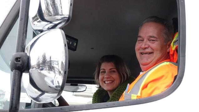 Une femme et un homme sourient à l'intérieur d'un camion