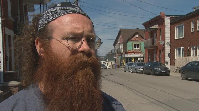 Yves Séguin en entrevue à l'extérieur, sur le bord d'une rue.