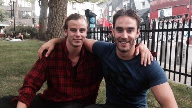 Les deux jeunes hommes sont bras dessus, bras dessous, assis sur l'herbe dans un parc.