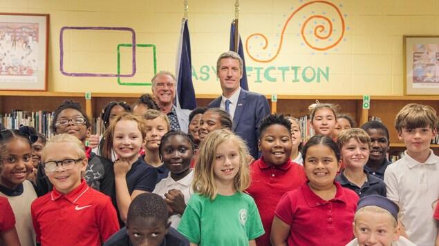 Zachary Richard en compagnie d'élèves dans une classe.
