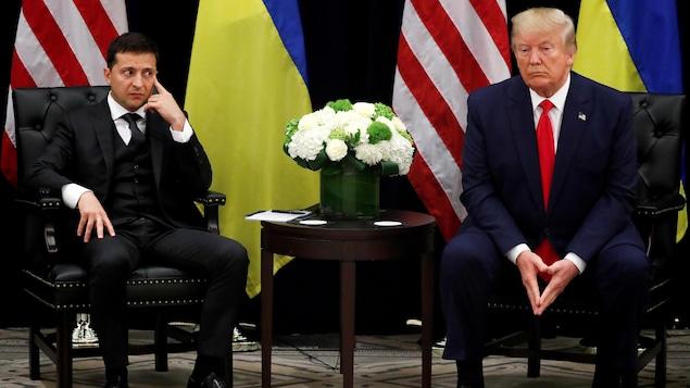 Volodymyr Zelensky et Donald Trump assis devant des drapeaux de l'Ukraine et des États-Unis, en point de presse.