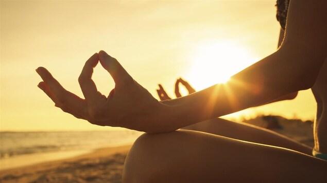 Une femme faisant de la méditation au coucher du soleil