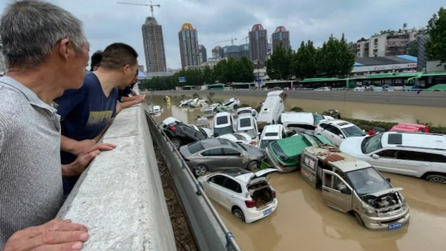 People look out at cars sitting in floodwaters after heavy rains hit the city of Zhengzhou in China's central Henan province on Wednesday.