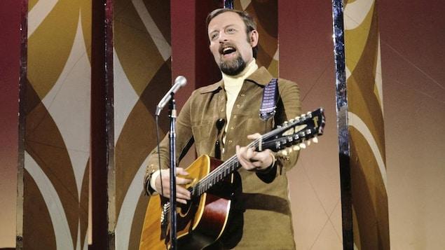 Roger Whittaker en performance sur scène avec sa guitare.