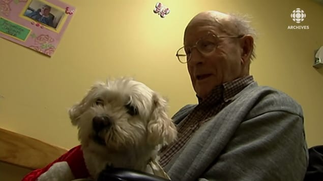 Un homme âgé qui tient un chien blanc dans ses bras.