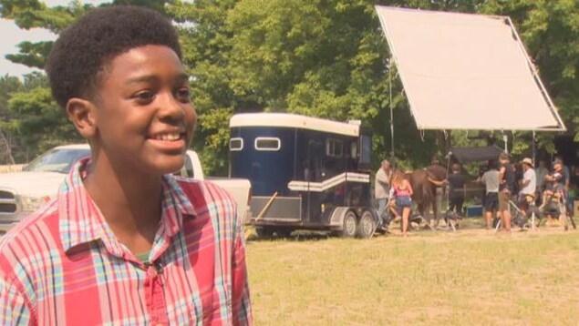 Zyon Allen porte une chemise rouge à carreaux, il a les cheveux noirs et crépus, il sourit à la caméra, derrière lui il la ferme