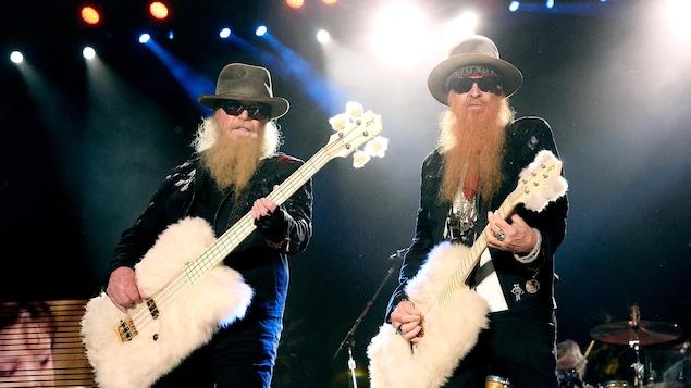 Les deux hommes portent chacun une longue barbe, des lunettes fumées foncées, un chapeau et un complet.